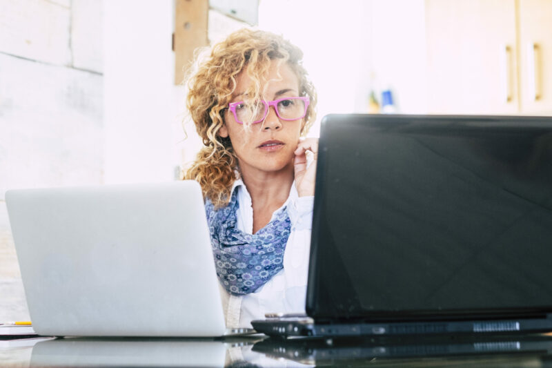 Data entry from a woman working on two laptops at once - being inefficient.