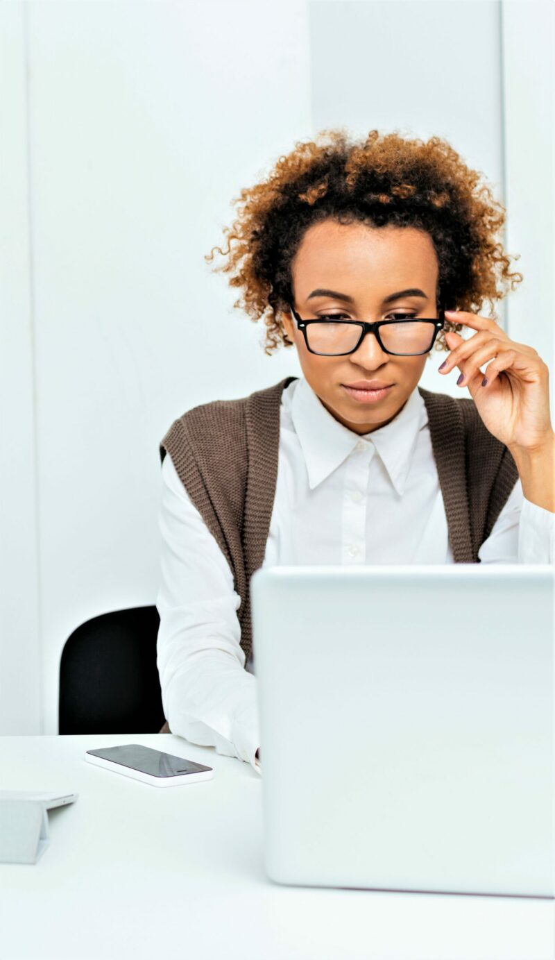 accountant with glasses working on payroll at her laptop